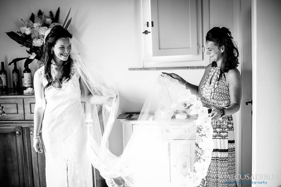 bride smiling holding the log white veil
