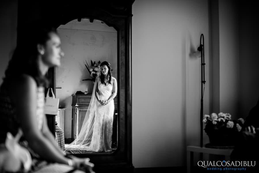 bride with white dress at mirror black and white