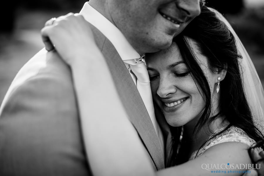 bride and groom smiling ambraced together black and white
