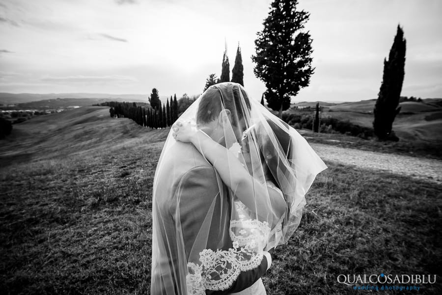 bride and groom embraced under the veil tuscany hills black and white