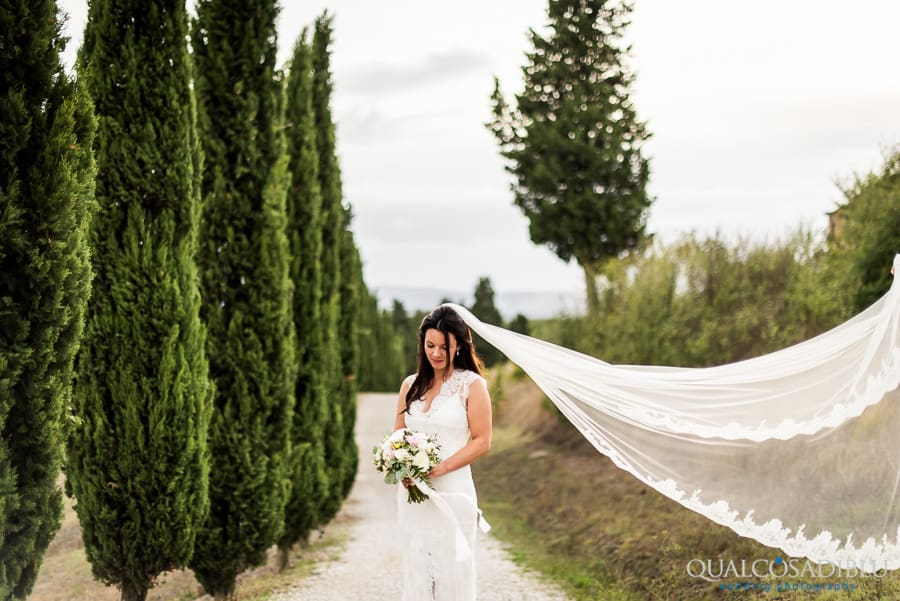 bride portrait with veil with cypresses in the background