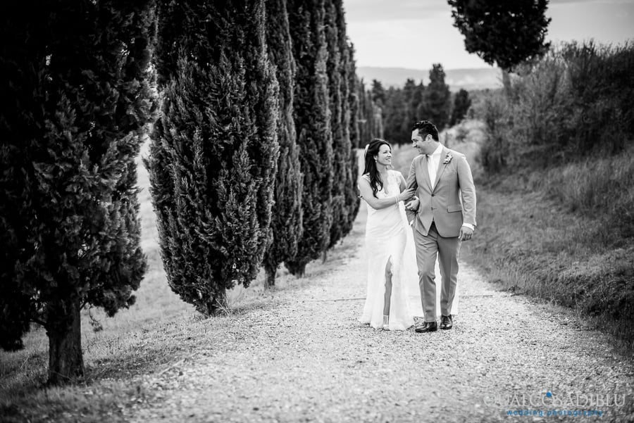 bride and groom walking cypresses black and white