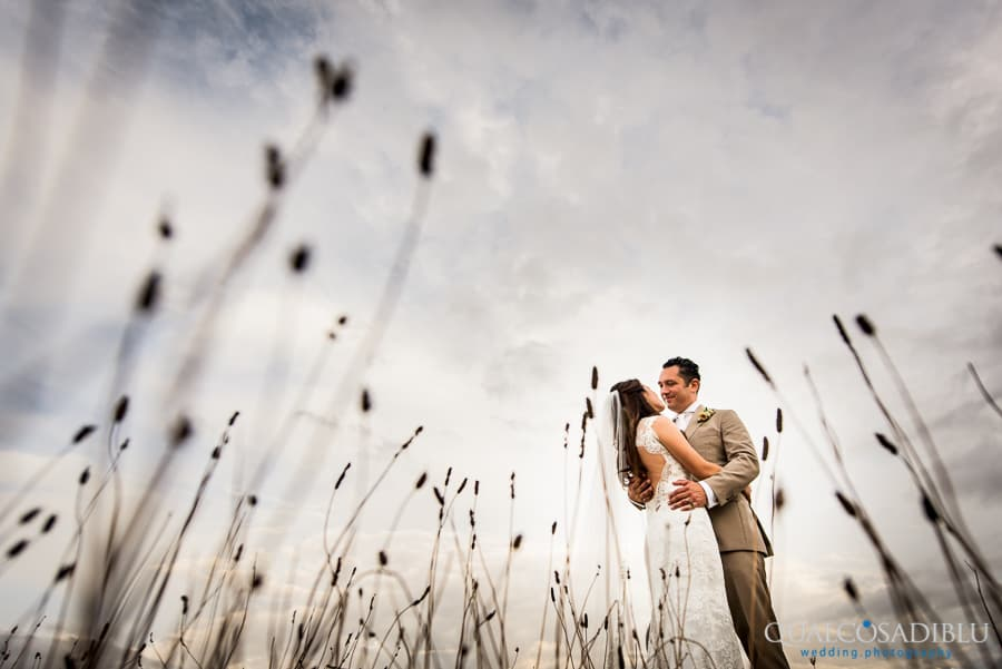 bride and groom embraced field grass