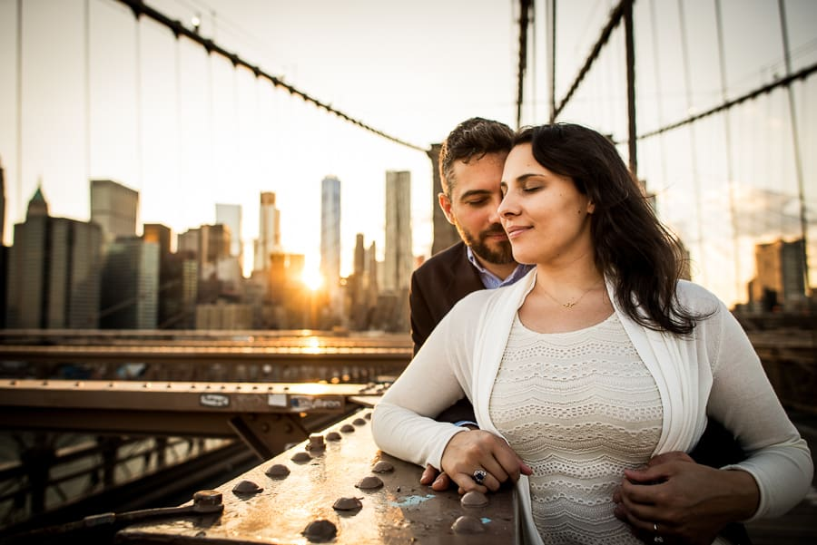 Couple embraced on brooklyn bridge and sylines in the background