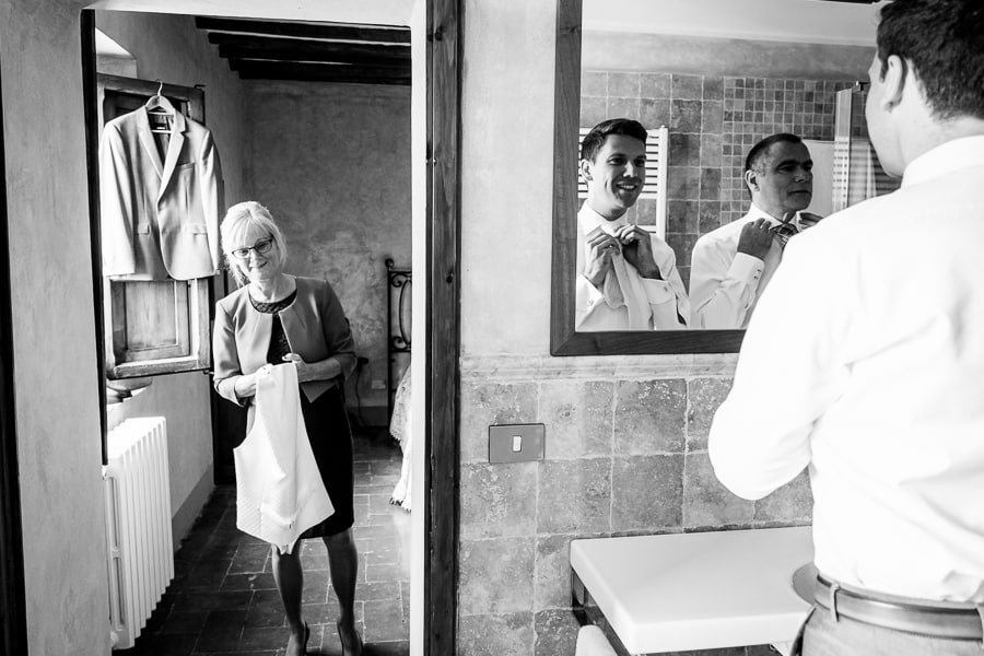 groom at mirror with parents