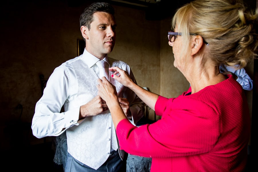 mother adjusting necktie groom