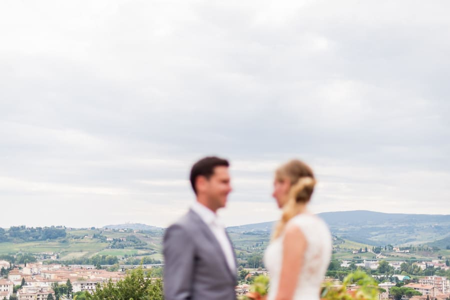 bride groom blurred with tuscany landscape backdrop