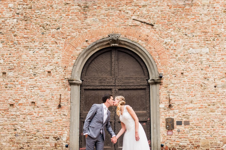 wedding couple kissing ancient big door certaldo