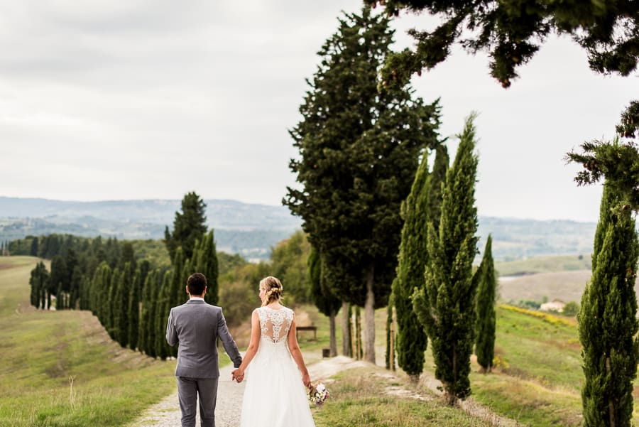 bride groom walking tuscany cypresses