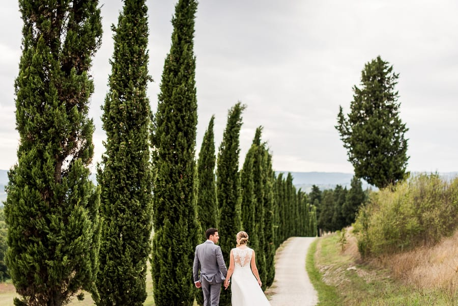 bride groom walking street tuscany cypresses