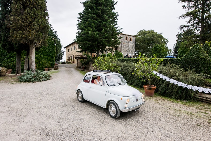 wedding couple arrives at fattoria di larniano fiat 500