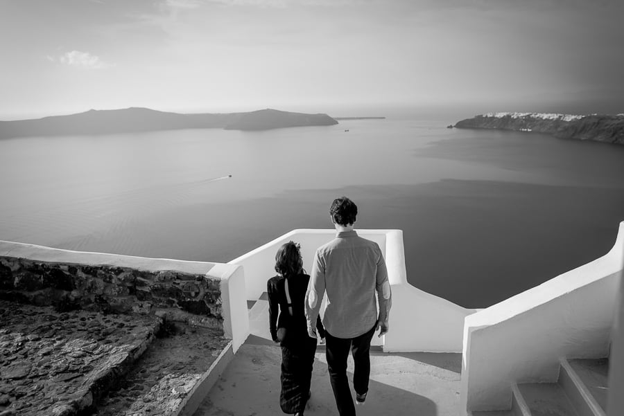 couple walking in santorini with caldera view