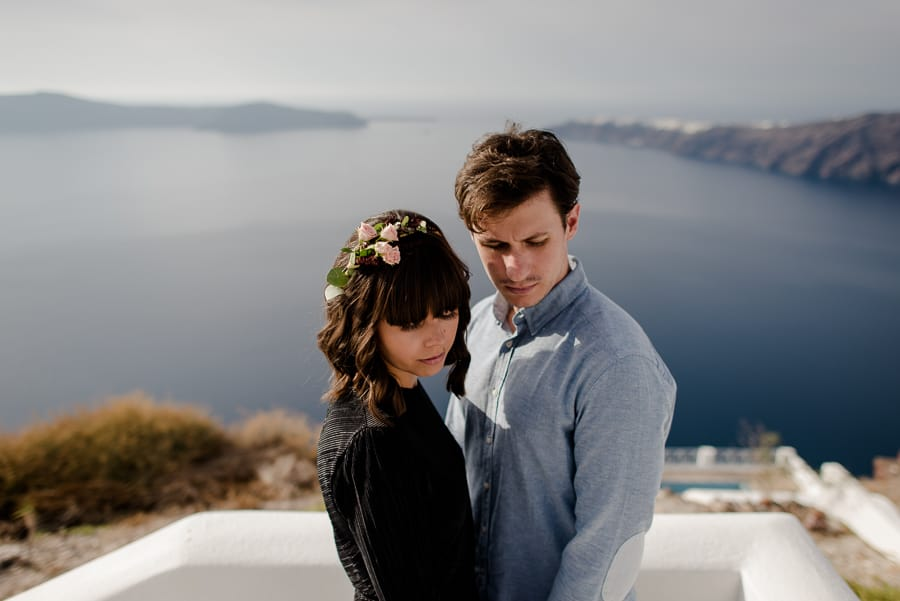 couple engaged in santorini with amazing view of caldera