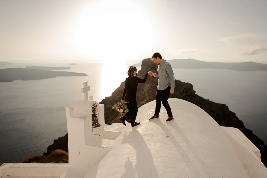 engaged coupleon the roof of a church with skaros rock view