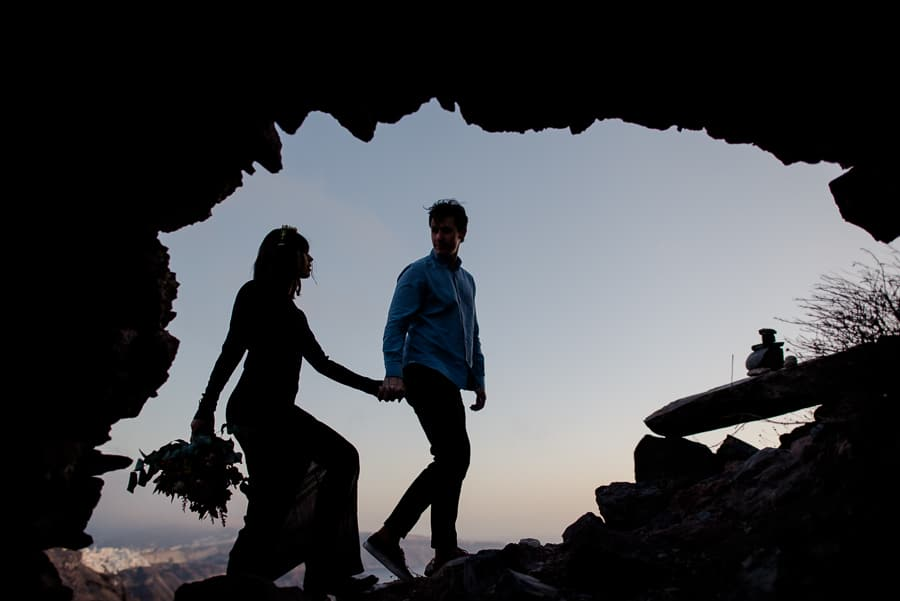 couple walking skaros rock cave