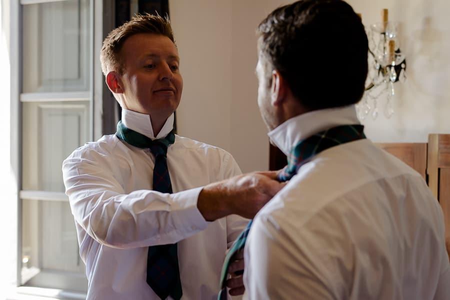 Bestman helping the groom with his necktie