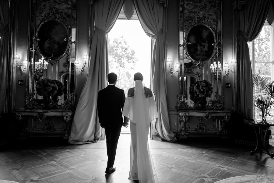 Bride and groom wlaking together inside the great hall in villa cora