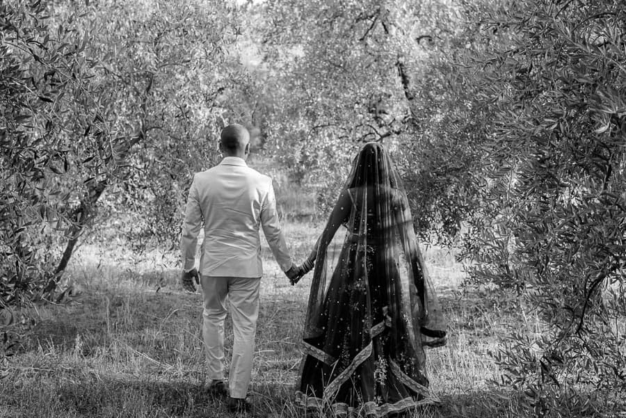 Bride and groom walking thru the olive trees in tuscany black and white