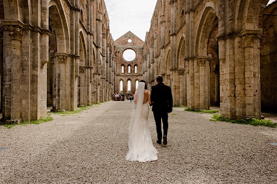 Bride walking with father down the aisle at San Galgano abbey