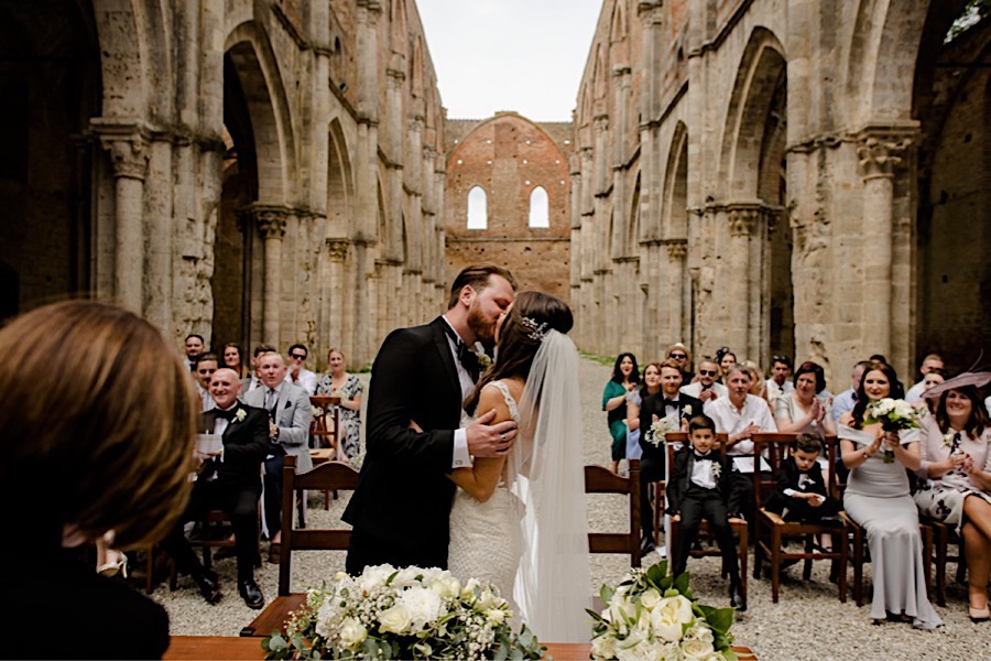 Bride and groom kissing each other during the ceremony at san galgano abbey
