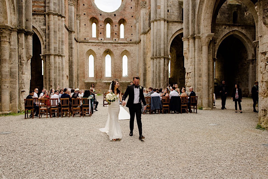 Bride and groom walking together after the wedding ceremony at san galgano abbey