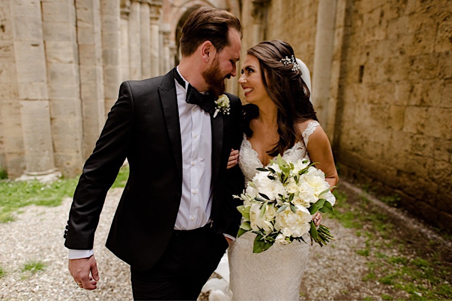 Bride and groom wlaking and smiling together at san galgano abbey