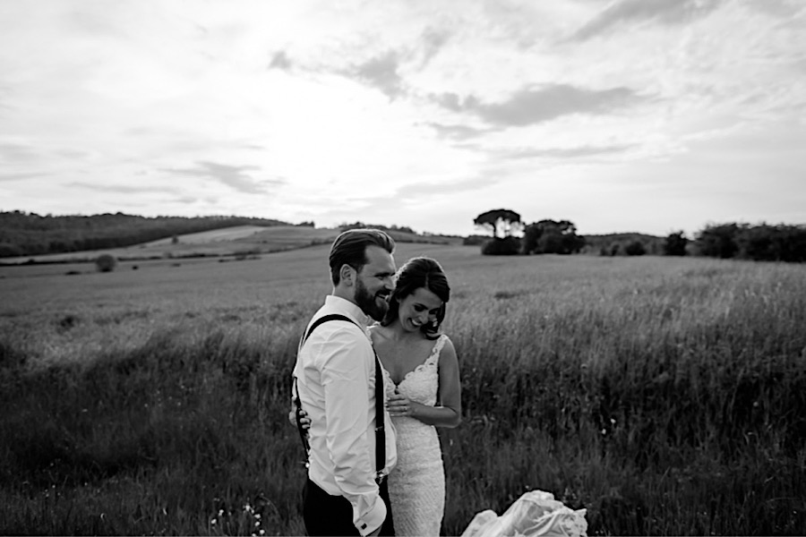 Bride and groom smiling on the tuscany countryside black and white photo