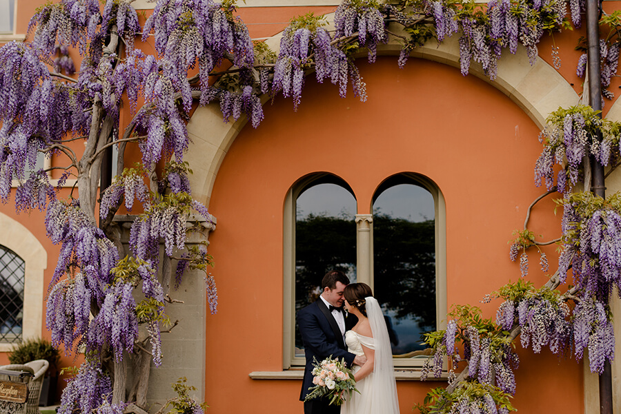 Bride and Groom portrait ahead to the window and with wisteria