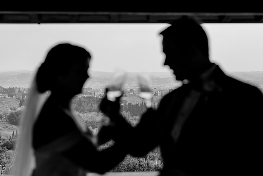 Newlywed couple having a toast with a panoramic view of Florence at Villa Le Fontanelle Black and White photo