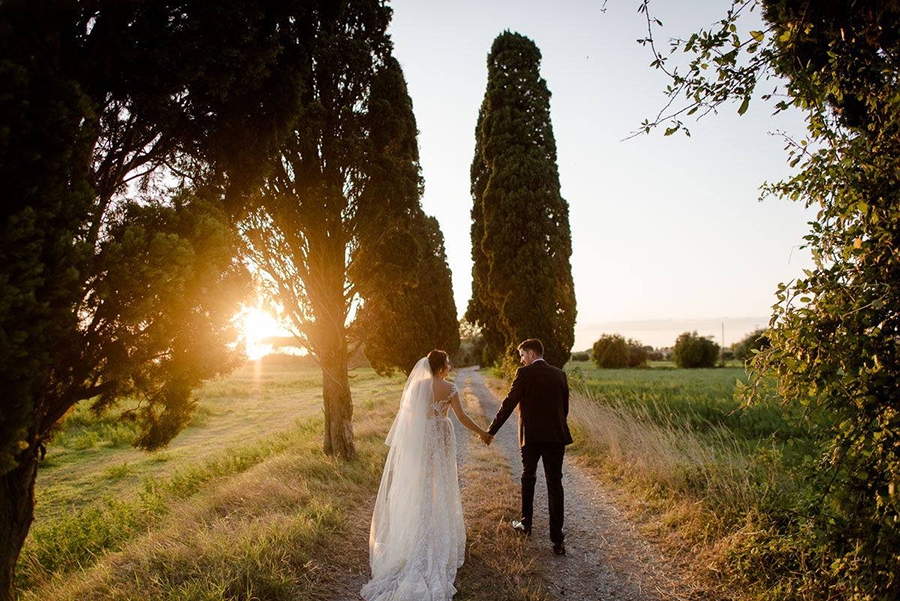 a wedding couple walking in tuscany during the golden hour in a cypresses road