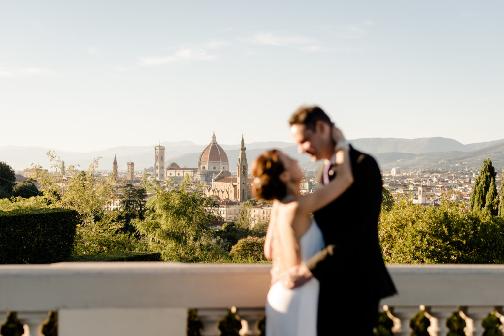 Romantic wedding couple kissing with the view of florence in the background