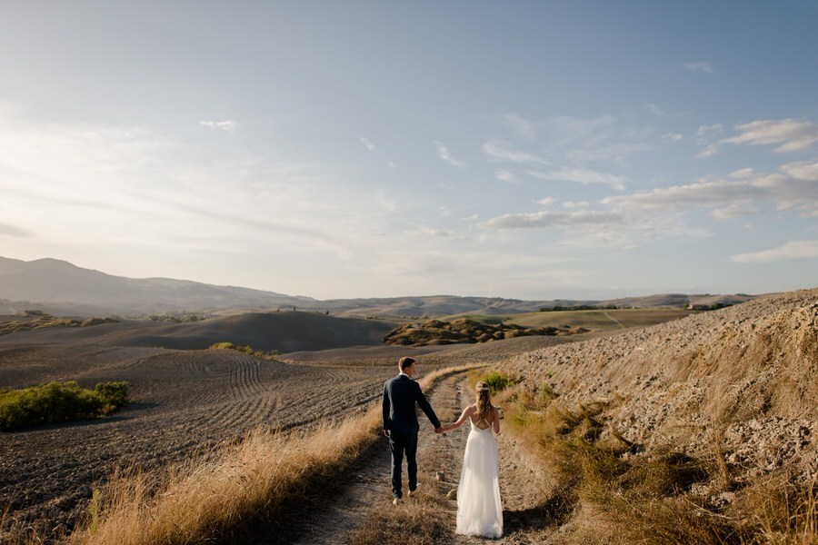 a couple walking in a breathtaking scenery in tuscany