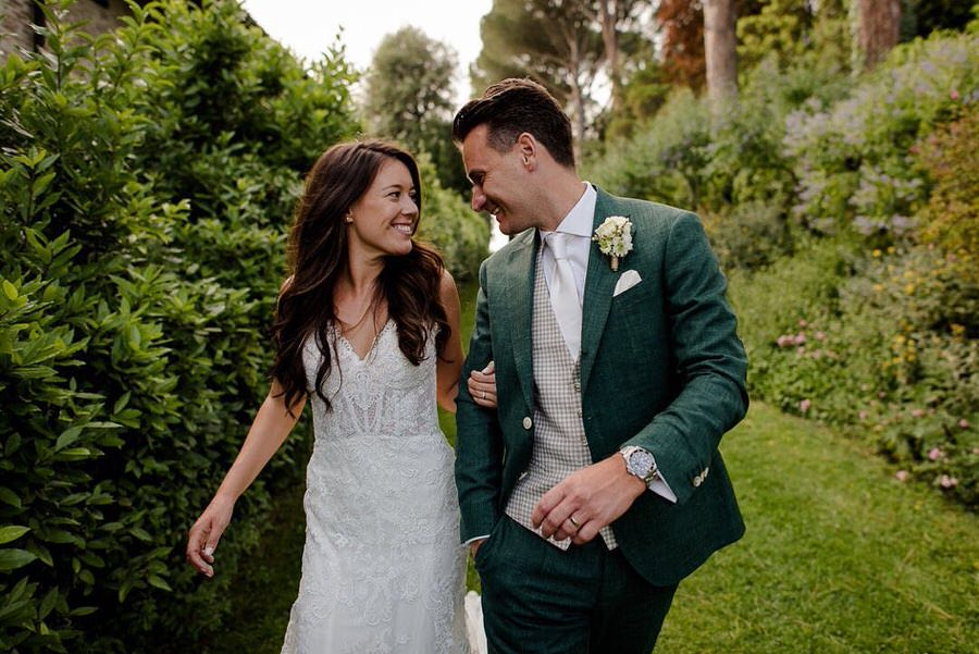 a beautiful wedding couple walking together and looking each other smiling