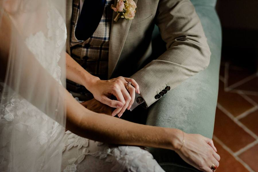 details of a wedding couple holding their hands