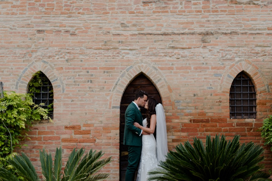 Bride and groom kissing each other at Tenuta di Pratello Country Resort