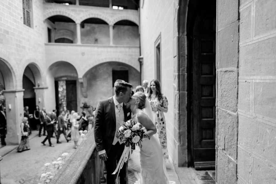 bride and groom kissing at montegufoni castle black and white