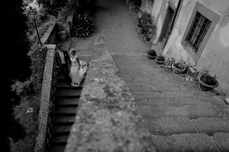 wedding couple walking down the stairs at montegufoni castle
