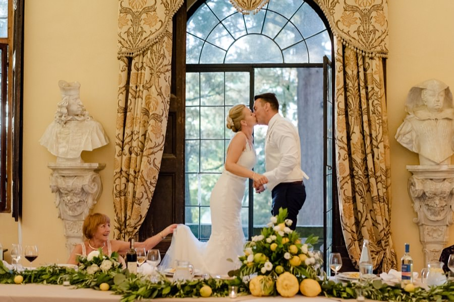 bride and groom stand on the chairs and kissing