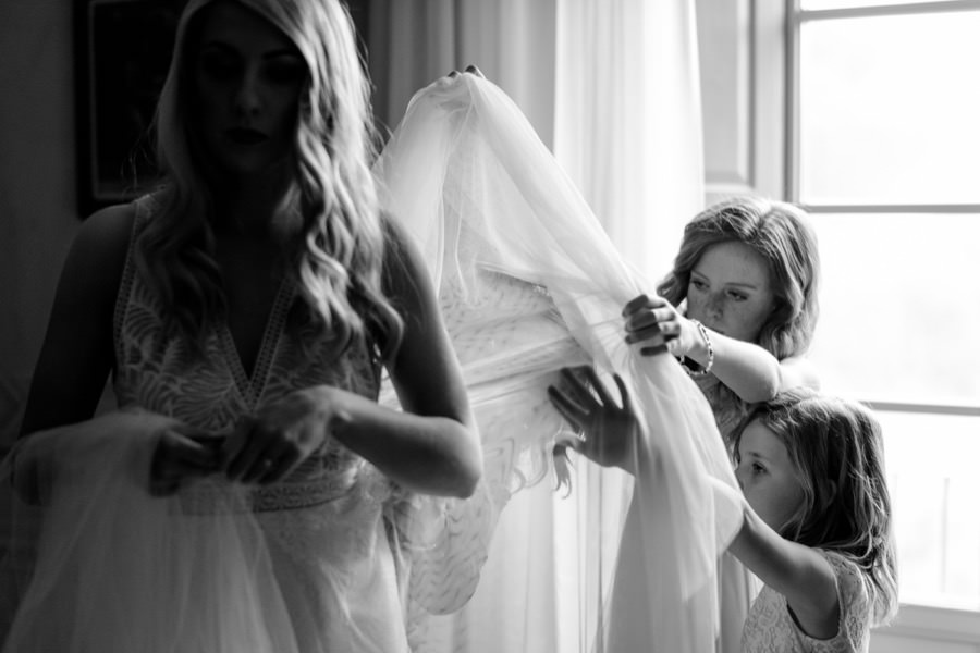 little bridesmaids helping the bride with the wedding dress black and white photo