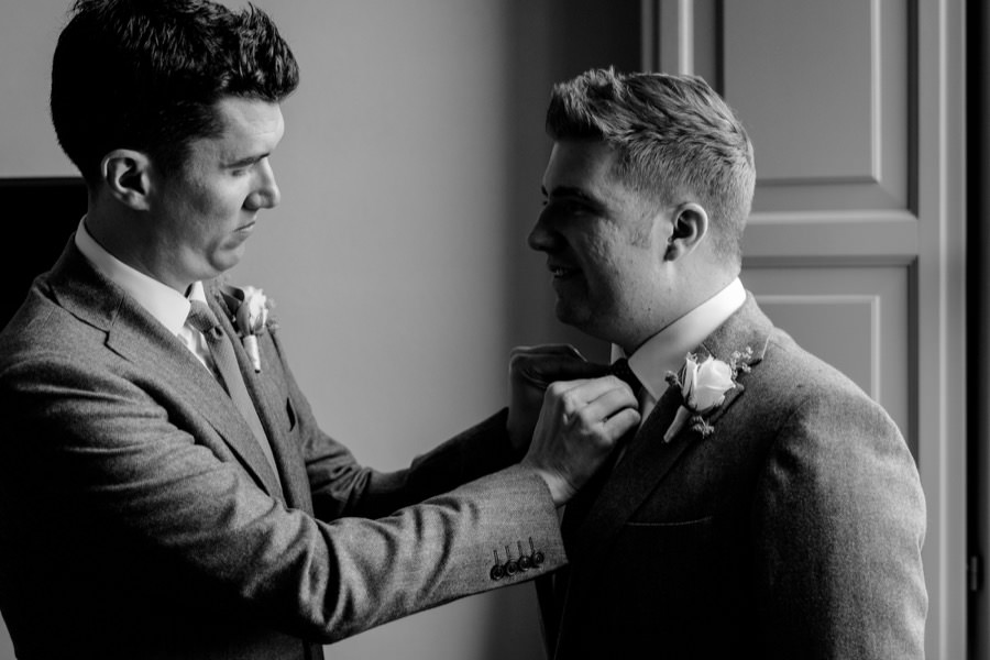 groom is helping his groomsman during the getting ready black and white photo