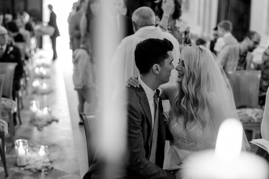 candid moment of the bride and groom kissing each other during the wedding ceremony