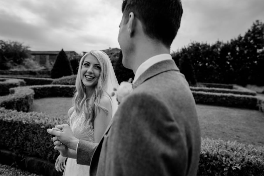 bride and groom walkins together black and white photo