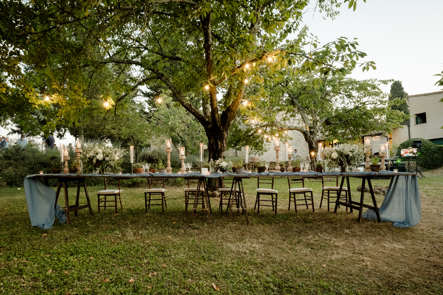 outdoor wedding dinner table setup with greenery