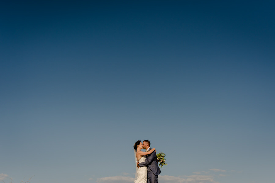 Bride and groom kissing with the sky in the background