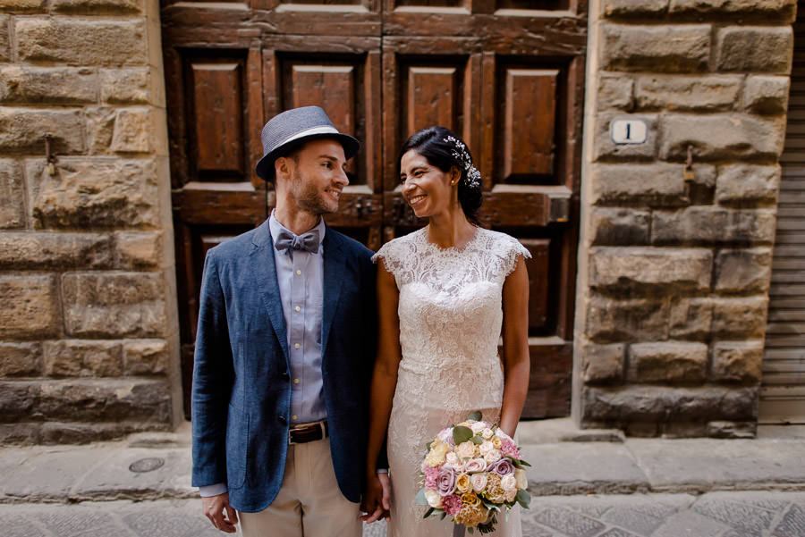 bride and groom in front of ancient big brown door in florence and smiling