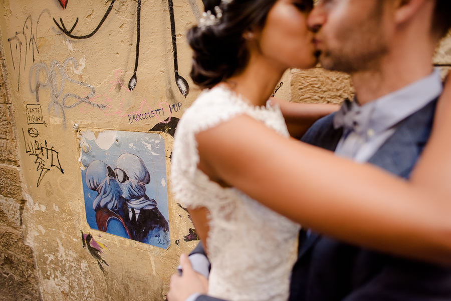 bride and groom are kissing in florence with a painted wall with graffitti as backdrop