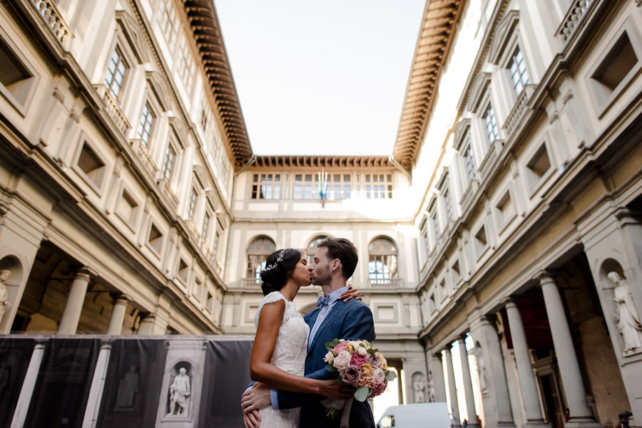 bride and groom kissing in florence with the uffizi building as backdrop
