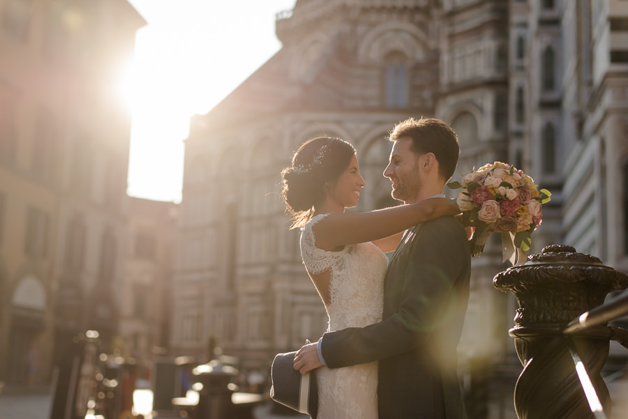 bride and groom embracing each other with t warm light in florence