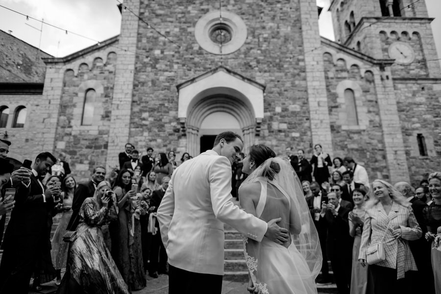 kiss of bride and groom in front of the church black and white