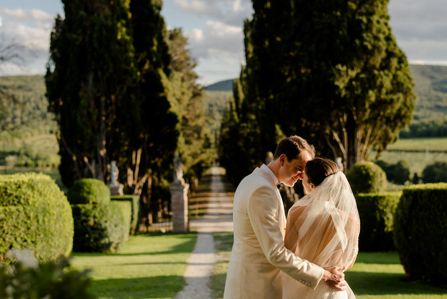 bride and groom kissing with the tuscan cypress road in the background